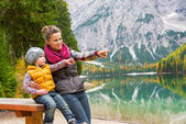Portrait of happy mother and baby on lake braies in south tyrol, — Stock Photo