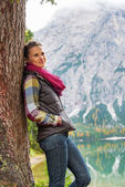 Young woman standing near tree on lake braies in south tyrol, it — Stock Photo
