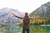 Young woman on lake braies in south tyrol, italy rejoicing. rear — Stock Photo