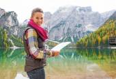Happy young woman with map on lake braies in south tyrol, italy — Stock Photo