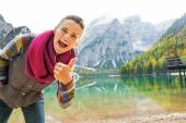 Happy young woman on lake braies in south tyrol, italy showing t — Stock Photo