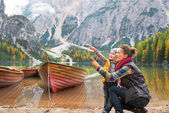 Happy mother and baby pointing on copy space while on lake braie — Stock Photo