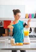 Счастливый фитнес молодая женщина, делающая тыквенный смузи в кухне — Стоковое фото