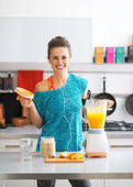 Portrait of happy fitness young woman making pumpkin smoothie in — Stock Photo