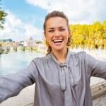 Smiling young woman making selfie on bridge ponte umberto I with — Stock Photo #64003353