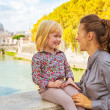 Happy mother and baby girl on bridge ponte umberto I with view o — Stock Photo #64003475