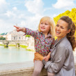 Happy mother and baby girl pointing while on bridge ponte umbert — Stock Photo #64003479