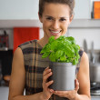 Portrait of happy young housewife with fresh basil — Stock Photo #64452935