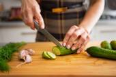 Closeup on young housewife cutting cucumber for pickling in kitc — Stock Photo