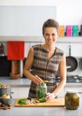 Portrait of happy young housewife pickling cucumbers in kitchen — Stock Photo