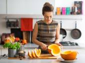 Young housewife cutting pumpkin in kitchen — Stok fotoğraf