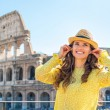 Portrait of happy young woman with audio guide in front of colos — Stock Photo #65069465
