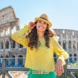 Happy young woman with audio guide in front of colosseum in rome — Stock Photo #65069567