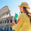 Happy young woman with italian flag in front of colosseum in rom — Stock Photo #65070315