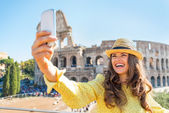 Smiling young woman taking photo with cell phone in front of col — Stock Photo