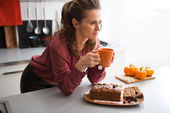 Happy young housewife drinking tea with freshly baked pumpkin br — Stock Photo