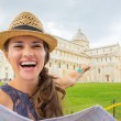 Happy young woman with map pointing on duomo di pisa, pisa, tusc — Stock Photo #65834145