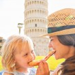 Happy mother and baby girl eating pizza in front of leaning towe — Stock Photo #65834551