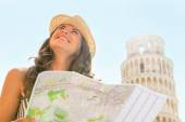 Happy young woman with map sightseeing in front of leaning tower — Stockfoto