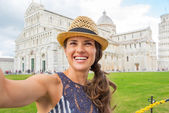Portrait of happy young woman making selfie on piazza dei miraco — Stock Photo