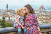 Mother and baby girl kissing against panoramic view of florence, italy — Stock Photo