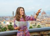 Happy young woman with map pointing against panoramic view of florence, italy — Stock Photo