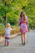 Mother and baby girl walking in city park. rear view — Stock Photo