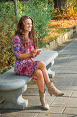 Happy young woman writing sms while sitting in city park — Foto de Stock
