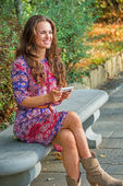 Happy young woman writing sms while sitting on bench in city par — Foto Stock