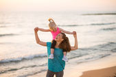 Happy baby girl sitting on shoulders of mother on beach in the e — 图库照片
