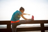 Closeup on fitness young woman stretching on beach in the evenin — Stock Photo