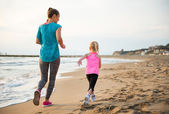 Healthy mother and baby girl running on beach. rear view — Stock Photo