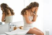 Stressed young woman sitting in bathroom — Stock Photo