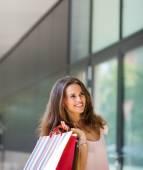 Leende kvinna shopping, håller upp färgglada påsar — Stockfoto