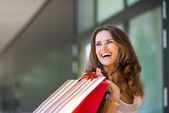 Happy woman out shopping, holding up colourful shopping bags — Stock Photo