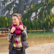 Portrait of smiling woman on Lake Bries readjusting scarf — Stock Photo #72465559