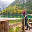 Woman hiker rests on a wooden railing, facing Lake Bries — Stock Photo #72465635