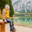 Blonde young girl sitting on picnic table at Lake Bries — Stock Photo #72465671