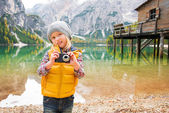Young blonde girl on shores of Lake Bries holding a camera — Stock Photo
