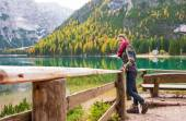 Woman hiker rests on a wooden railing, facing Lake Bries — Stock Photo