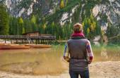 Woman hiker looking out at wooden boats and pier on Lake Bries — Stock Photo