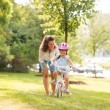 Mother teaching her daughter how to ride a bicycle in a park — Stock Photo #72933599