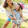 Laughing mother and daughter learning how to ride a bike — Stock Photo #72933615