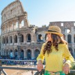 Smiling woman tourist relaxing near Colosseum in Rome in summer — Stock Photo #73505167