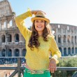 Smiling woman holding hat near Colosseum in Rome in summer — Stock Photo #73505169