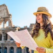 Smiling woman holding map of Rome at Colosseum in Rome — Stock Photo #73505205