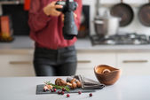 Woman photographer focuses lens autumn fruits and vegetables — Stock Photo
