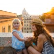 Mother kneeling by daughter above Rome at sunset — Stock Photo #74193259