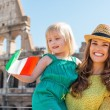 Smiling mother and daughter waving Italian flag by Colosseum — Stock Photo #74193271
