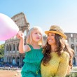 Smiling mother and daughter with pink balloon by Colosseum — Stock Photo #74193279